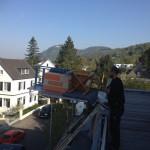Ein Mitarbeiter hat die Ladefläche des Lastenaufzugs beladen. Im Hintergrund sieht man unter blauem Himmel das Siebengebirge.