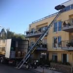 Vor einem gelben Mehrparteienhaus steht ein Umzugs-LKW. Ein Lastenaufzug ist am Haus aufgestellt und reicht bis zur Dachterrasse im dritten Stockwerk.