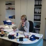 Eine Mitarbeiterin sitzt in einem Büro und telefoniert.