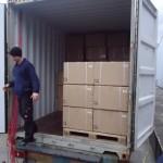 In einer geöffneten, grauen Wechselbrücke sind Kartons gestapelt. Ein Mitarbeiter mit Wollmütze steigt gerade aus der Wechselbrücke.