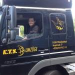 In der Fahrerkabine eines schwarzen Umzugs-LKW sitzt ein lächelder Mitarbeiter am Steuer.