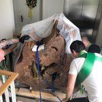 Männer heben einen schweren Tischfuß (Baumstamm)