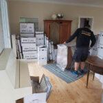 Wohnzimmer mit Umzugskartons und KTS-Mitarbeiter